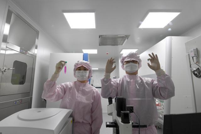 연구원들이 백신의 역가시험을 위한 세포배양액과 검체(백신)를 들어보이고 있다.