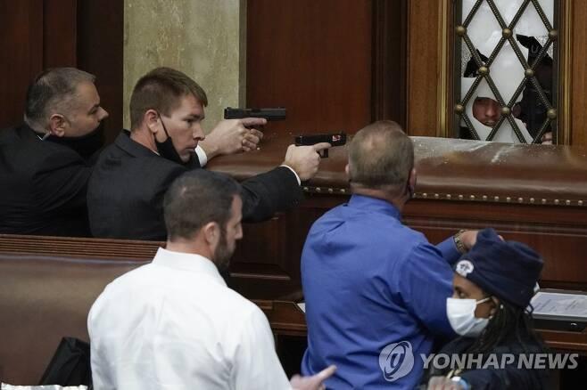 하원 회의장 진입하려는 시위대에 권총 겨눈 미 의회 경찰 [AP=연합뉴스]