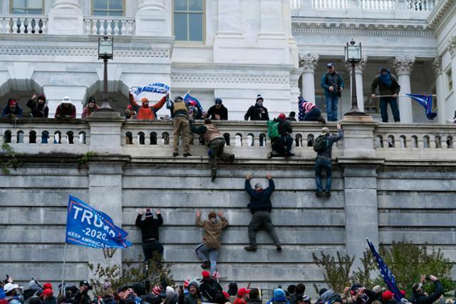 도널드 트럼프 미국 대통령 지지 시위대가 6일 워싱턴 연방의회 의사당 서쪽 벽을 기어오르고 있다. 워싱턴=AP 연합뉴스