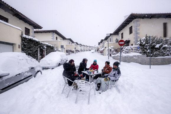 - 이웃들이 9일(현지시간) 스페인 마드리드 외곽의 부스타비조에서 폭설이 내리는 동안 거리 한복판에서 술을 마시고 있다. 지속적인 눈보라가 스페인의 많은 지역을 50년 동안의 기록적인 눈의 수준으로 뒤덮었다. AP 연합뉴스