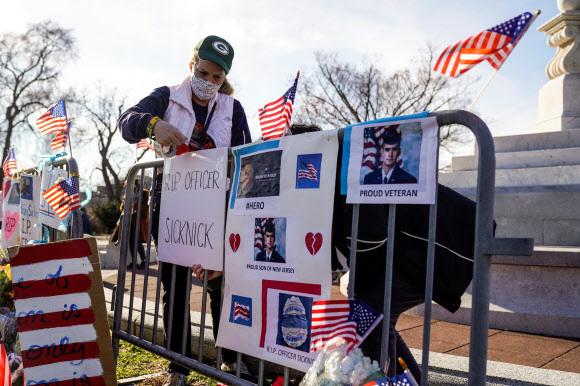 미국 여성 앤느 세이무어가 지난 6일(이하 현지시간) 도널드 트럼프 대통령의 대선 불복을 지지하는 시위대가 의사당에 난입했을 때 세상을 떠난 브라이언 시크닉 의회경찰관을 추모하는 장식을 10일 꾸미고 있다. 비번이던 의회경찰관 하워드 리벤굿이 지난 9일 극단을 선택한 사실이 이날 알려졌다.워싱턴 DC 로이터 연합뉴스