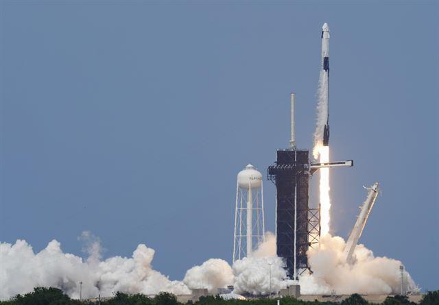 미 항공우주국(NASA) 우주비행사 더글러스 헐리와 로버트 벤킨이 크루 드래건에 탑승한 스페이스X 팰컨9호가 지난해 5월 미 플로리다주 케이프 커내버럴의 케네디 우주센터 39-A 발사대에서 발사되고 있다. 팰컨9는 테슬라 최고경영자(CEO) 일론 머스크가 설립한 우주탐사 기업 스페이스X가 민간기업 최초로 발사한 민간 유인 우주선으로 민간 우주여행 시대의 새로운 이정표를 세웠다. AP 뉴시스