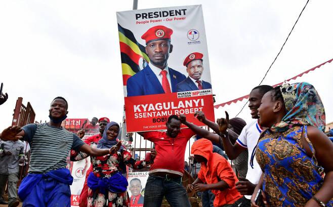 35년간 집권한 요웨리 무세베니 우간다 대통령에 맞서 야당 대통령 후보로 출마한 래퍼 출신 정치인 보비 와인(본명 로버트 캬굴라니 센타무)의 지지자들이 12일(현지시간) 우간다 캄팔라 거리에서 춤추며 선거 유세를 하고 있다. 캄팔라 | 로이터연합뉴스