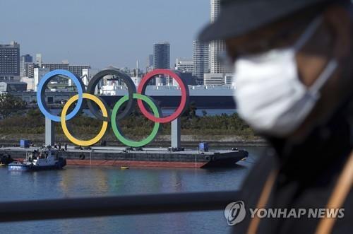 (도쿄 AP=연합뉴스) 지난달 1일 일본 도쿄도(東京都)에서 마스크를 쓴 남성이 이동하는 가운데 오다이바 해변 공원에 도쿄올림픽을 상징하는 조형물이 보인다. 신종 코로나바이러스 감염증(코로나19)이 급격하게 확산하면서 도쿄 올림픽·패럴림픽 개최가 어렵다는 관측이 대두하고 있다.