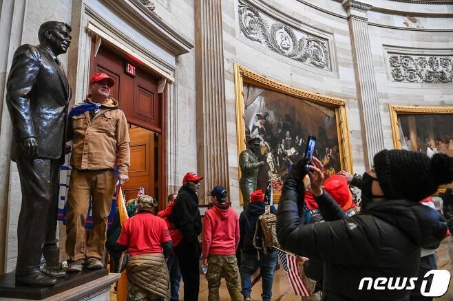 6일(현지시간) 워싱턴 의사당에 난입한 도널드 트럼프 미국 대통령을 지지하는 시위대가 기념촬영을 하고 있다. © AFP=뉴스1 © News1 우동명 기자