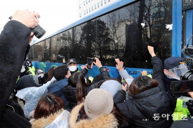 정인이를 학대해 숨지게 한 양부모에 대한 첫 재판이 13일 서울 양천구 서울남부지법에서 열렸다. 재판 후 양모가 탄 법무부  호송차량이 법원을 빠져나가려고 하자 시민들이 길을 막아선 채 눈을 뭉쳐 던지고 차량을 두드리는 등 분노를 드러냈다. 양회성 기자  yohan@donga.com