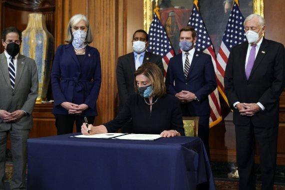 낸시 펠로시 미국 하원의장(민주당)이 13일(현지시간) 워싱턴 DC 의회 의사당에서 하원이 표결로 통과시킨 도널드 트럼프 대통령 탄핵소추안에 서명하고 있다. 미 하원은 트럼프 대통령을 의회 의사당 난입사건 관련 내란 선동 혐의로 탄핵소추안 표결을 실시해 찬성 232표, 반대 197표로 통과시켰다. AP뉴시스