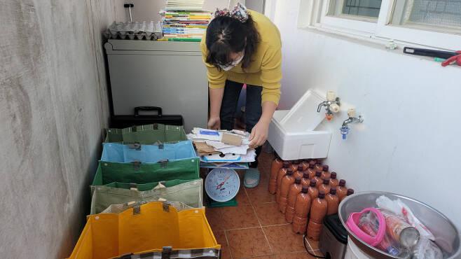지난 13일 오후 충북 청주시 흥덕구 비하동 한 아파트에서 청주새활용시민센터가 진행하는 '쓰레기 줄이기 100일간의 실험'에 참여한 노설희씨가 자신의 집 뒷베란다에서 저울을 이용해 쓰레기 무게를 측정하고 있다.