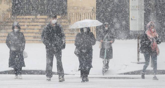 18일 오전 서울 강남구 청담사거리 인근에서 눈이 내리는 가운데 시민들이 발걸음을 재촉하고 있다. 뉴스1