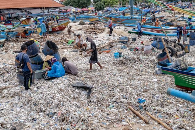 인도네시아 발리 끄동아난의 어촌마을에서 18일 어부들이 플라스틱 쓰레기가 덮인 해변에서 작업을 하고 있다. 발리의 유명한 해변들은 몬순으로 인해 해안으로 밀려온 수많은 플라스틱 쓰레기에 묻혀 있다. 환경전문가들은 몬순, 열악한 폐기물 관리와 세계적인 해양오염위기가 이같은 상황을 연례행사처럼 만들고 있다고 말한다. 발리=EPA 연합뉴스