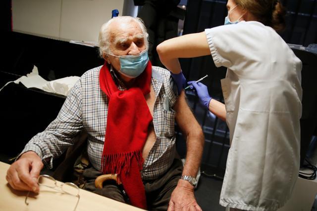 18일 프랑스 파리 제7구의 한 백신 접종센터에서 94세 노인이 화이자ㆍ바이오엔테크의 코로나19 백신 주사를 맞고 있다. 파리=AP 연합뉴스