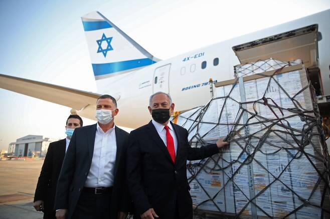 베냐민 네타냐후 이스라엘 총리와 율리 에델스타인 보건부 장관이 지난 10일 수도 텔아비브 근처 벤구리온 공항에서 화이자/바이오N테크의 코로나백신 물량을 싣고 도착한 비행기를 배경으로 기념행사를 갖고 있다. 네타냐후 총리는 최근 화이자 백신만으로도 16세 이상 인구 모두를 접종할 수 있는 물량을 계약했다고 밝혔다./AFP 연합뉴스
