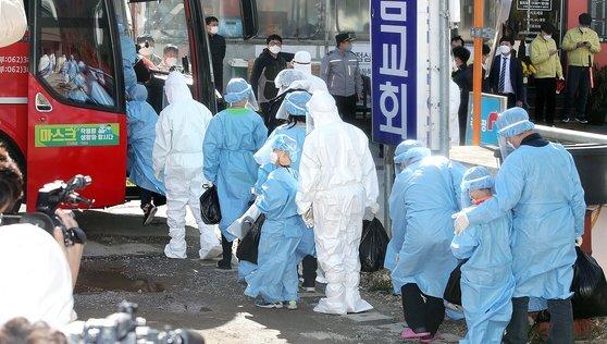 광주 광산구 운남동 광주 TCS 국제학교에서 확진자들이 치료 센터로 향하는 이송 버스에 오르고 있다. 연합뉴스
