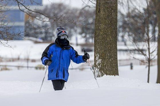16일 폭설이 내린 미 일리노이의 공원에서 시민이 스키로 이동하고 있다. [EPA=연합뉴스]