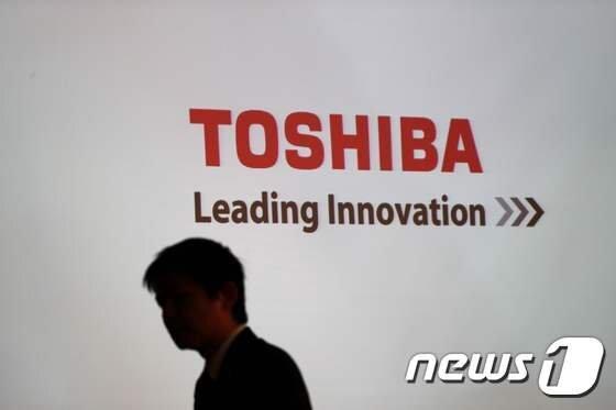 일본 도시바 본사 로비에 새겨진 회사 로고 앞으로 한 남성이 지나가고 있다. 자료사진. AFP뉴스1