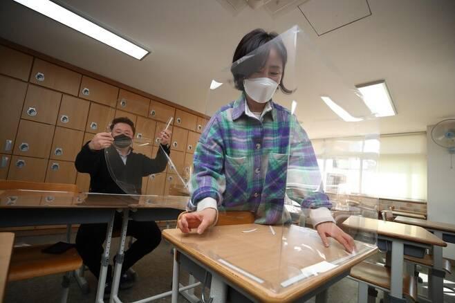 23일 오전 대구 남구 대명동 경북예술고등학교에서 교사들이 개학 뒤 학생들의 등교에 대비해 코로나19 확산 예방을 위한 투명 가림판을 교실 내 책상에 설치하고 있다. 사진 연합뉴스