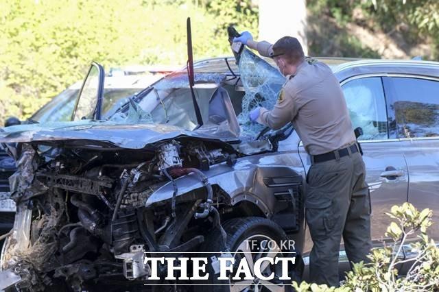 앞부분이 크게 부서진 우즈의 사고 차량을 살피는 사고처리담당관./LA=AP.뉴시스