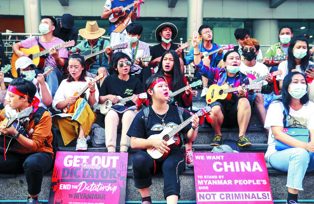 군부 쿠데타를 규탄하는 미얀마 시민들이 23일 양곤에서 기타와 우쿨렐레 등 악기를 연주하며 시위를 벌이고 있다. 이들 앞에는 '테러리스트 독재자는 물러가라' '중국은 범죄자들이 아닌 미얀마 국민의 편에 서라'는 영문 문구가 적힌 팻말이 놓여 있다. AP연합뉴스