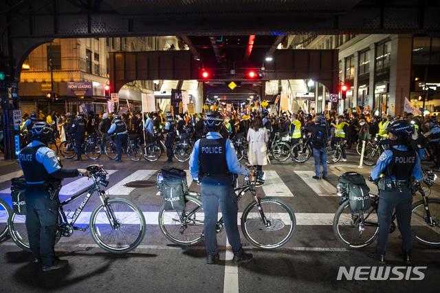 [시카고=AP/뉴시스]도널드 트럼프 미국 대통령이 일부 경합 주에 대해 개표 중단 소송을 제기한 가운데 4일(현지시간) 미 일리노이주 시카고에서 시카고 경찰이 약 1000명의 시위대가 모든 표를 개표할 것을 촉구하며 행진하는 모습을 지켜보고 있다. 2020.11.05.