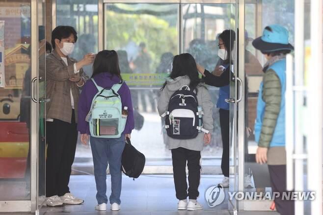 서울의 한 초등학교에서 학생들이 교실로 들어가기 전 발열 체크를 받고 있다. [연합뉴스 자료사진]