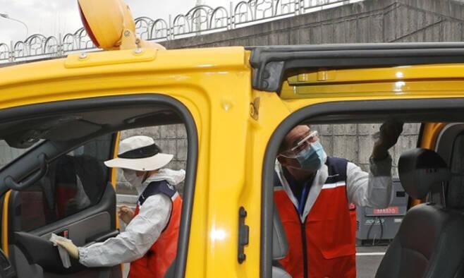 24일 오전 울산시 중구 동천체육관 주차장에 마련된 '개학맞이 굿바이 코로나 울산 방역 정류장'에서 자원봉사자들이 차량을 소독하고 있다. 울산=연합뉴스