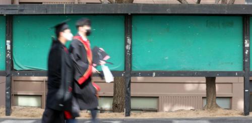 졸업생들이 지난 18일 서울 시내 한 대학교에서 기념촬영을 위해 이동하고 있다. 졸업생들 뒤로 기업 인턴 및 채용정보가 부착되는 게시판이 텅텅 비어 있는 모습이 보인다. /연합뉴스