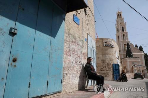 강력한 봉쇄조치 속에 집앞에 나와 앉은 팔레스타인 서안 주민 [AFP=연합뉴스 자료사진]