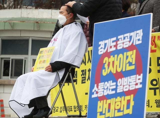 25일 수원 광교 주민이 도청 앞에서 경기도 공공기관 3차 이전에 반대하며 삭발 시위를 벌이고 있다. 연합뉴스