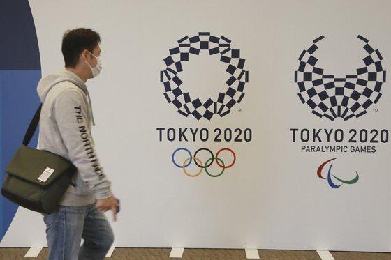 전세계적인 백신 보급으로 코로나19가 진정 기미를 보이면서 도쿄올림픽을 정상 개최하려는 일본 정부와 조직위원회의 의지에 힘이 실리고 있다. 올림픽 엠블럼 앞을 지나는 도쿄 시민. [AP=연합뉴스]
