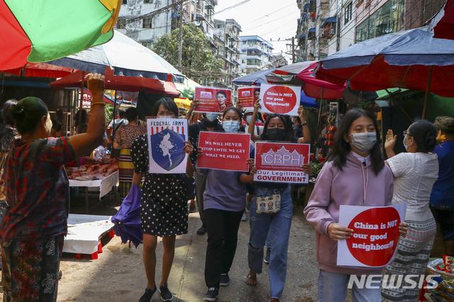 """[양곤=AP/뉴시스]7일(현지시간) 미얀마 양곤에서 반 쿠데타 시위대가 """"중국은 좋은 이웃이 아냐"""" """"우리는 멈추지 않는다"""" 등이 쓰인 팻말을 들고 상인들의 환영을 받으며 시장을 행진하고 있다. 2021.04.07"""