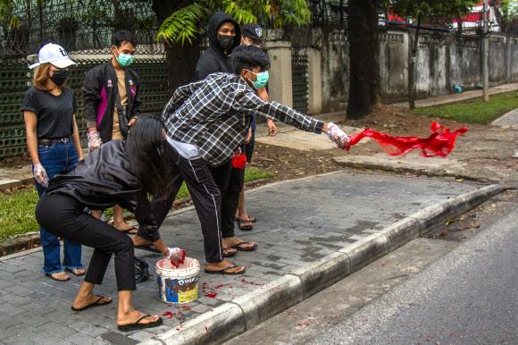 지난 6일(현지시간) 미얀마 양곤에서 반 쿠데타 시위대가 거리에 붉은 페인트를 뿌리고 있다. 양곤=AP·뉴시스