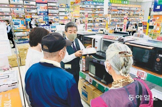 73세 판매 사원인 사토 다다시 씨(왼쪽에서 세 번째)가 가나가와현 후지사와시의 '노지마' 가전 매장에서 고령의 고객들에게 전자레인지의 성능에 대해 설명하고 있다. 후지사와=김범석 특파원 bsism@donga.com
