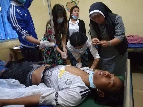 누 따웅 수녀가 가톨릭 교회가 연 치료 센터에서 부상 당한 시민을 치료하며 산모의 출산을 돕고 있다. [누 따웅 수녀 제공]