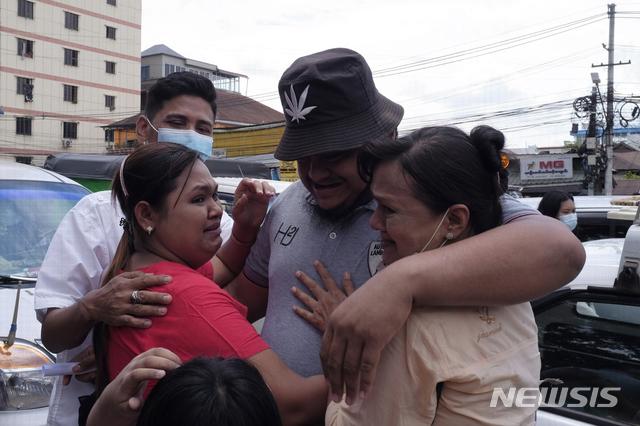 [양곤=AP/뉴시스] 17일 미얀마 양곤의 한 교도소에서 출소하는 한 제소자가 가족들과 포옹하고 있다. 미얀마 군부가 최대 축제이자 전통 설인 띤잔(Thingyan)을 맞아 이날 대규모 사면을 단행했다. 2021.04.17