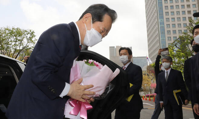정세균 국무총리가 16일 서울 종로구 정부서울청사에서 환송식을 마친후 꽃다발을 들고 인사하고 있다. 뉴스1