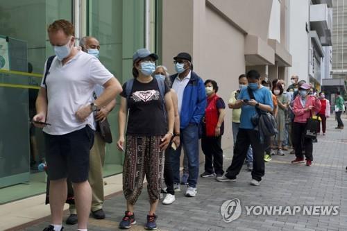 (홍콩 AP=연합뉴스) 지난 6일 홍콩의 한 신종 코로나바이러스 감염증(코로나19) 백신 접종 센터 앞에서 시민들이 줄지어 서 있다.