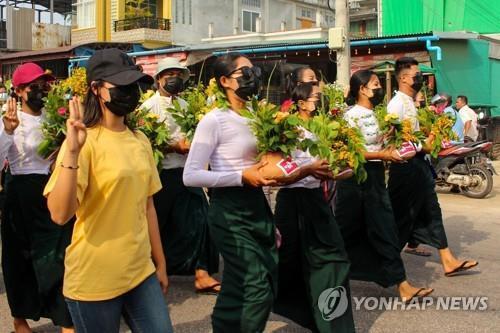 다웨이에서 띤잔 축제 꽃이 든 화분을 들고 세손가락 경례를 하며 행진하는 여성들 [다웨이 워치/AFP=연합뉴스. 재판매 및 DB 금지]