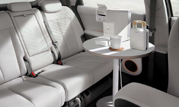 뒷좌석 바닥에 탁자를 놓고 커피머신을 좌석 아래 220V 콘센트에 연결해 사용하는 모습.