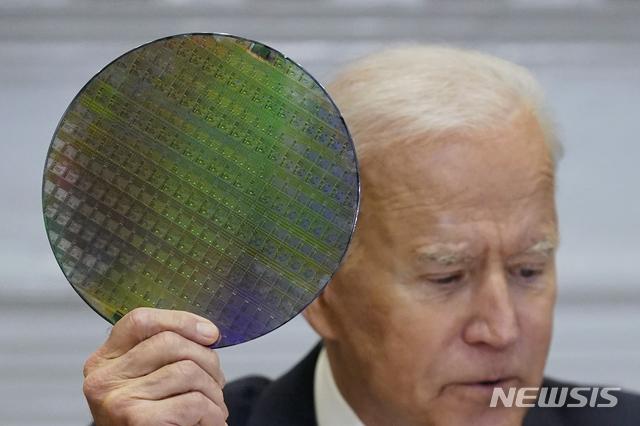 [워싱턴=AP/뉴시스]12일(현지시간) 미국 워싱턴 백악관 루즈벨트룸에서 열린 반도체 공급망 관련 회의에서 조 바이든 대통령이 반도체 웨이퍼를 들어보이고 있다. 2021.04.13.