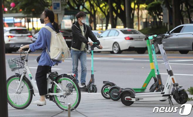 전동킥보드 등 개인형 이동장치(PM)의 이용 규제를 강화하는 개정 도로교통법 시행을 하루 앞둔 12일 서울의 한 도로에서 전동킥보드와 공유자전거를 탄 시민들이 헬멧 없이 주행하고 있다.  2021.5.11/뉴스1 © News1 이성철 기자