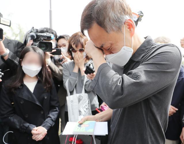 고(故) 손정민씨의 아버지 손현씨가 어버이날인 8일 오후 서울 서초구 반포한강공원 수상택시승강장 앞에서 아들의 그림을 선물로 받은 후 눈물을 흘리고 있다. 뉴스1