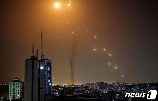 11일(현지시간) 팔레스타인 자치 지역인 가자지구 상공에서 무장 정파 하마스가 쏜 로켓포를 이스라엘 방공시스템 아이언돔의 미사일이 요격을 하고 있다. © AFP=뉴스1 © News1 우동명 기자