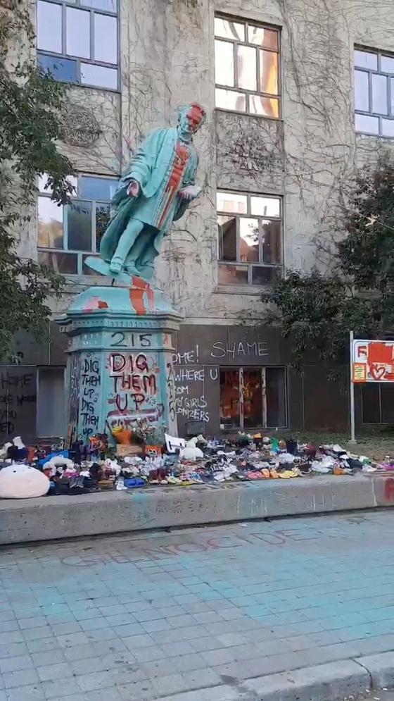 지난 6일(현지시간) 캐나다 토론토 라이어슨대에서 시위대가 라이어슨 목사의 동상을 끌어내리고 있다. 이튿날 훼손된 동상 일부는 개발반대 시위 현장에 옮겨졌다.〈사진=로이터〉