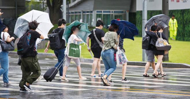 이상기후에 따른 변덕스러운 날씨가 이어지면서 시민들이 피로감을 호소하고 있다. 사진은 비바람이 몰아치는 서울 용산구 용산역 앞 횡단보도를 시민들이 힘겨워하며 건너는 모습ⓒ시사저널 최준필