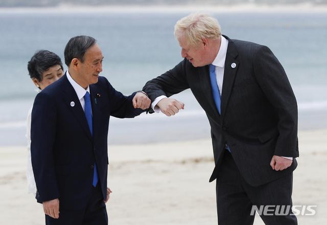 [콘월=AP/뉴시스]지난 11일(현지시간) 스가 요시히데 일본 총리(왼쪽)과 보리스 존슨 영국 총리가 콘월 카비스베이 해변에서 주요 7개국(G7) 정상회의 기념촬영에 임하기 전 팔꿈치 인사를 하고 있다.