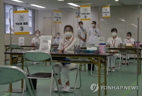 (도쿄 EPA=연합뉴스) 지난달 24일 일본 도쿄도(東京都)에 설치된 대규모 접종 센터에서 의료진이 신종 코로나바이러스 감염증(코로나19) 백신을 맞을 방문자를 기다리고 있다.