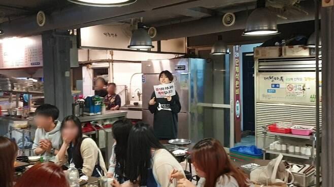 냉동 돼지를 파는 한 육식 식당에서 은영 활동가가 방해시위를 하고 있다.