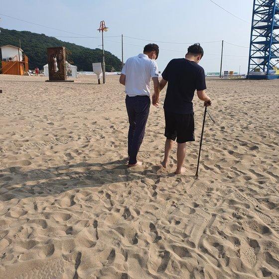김호영(오른쪽)씨가 바닷가 모래밭에서 아버지의 부축을 받으면서 걷고 있다 .사진 김두경씨 제공