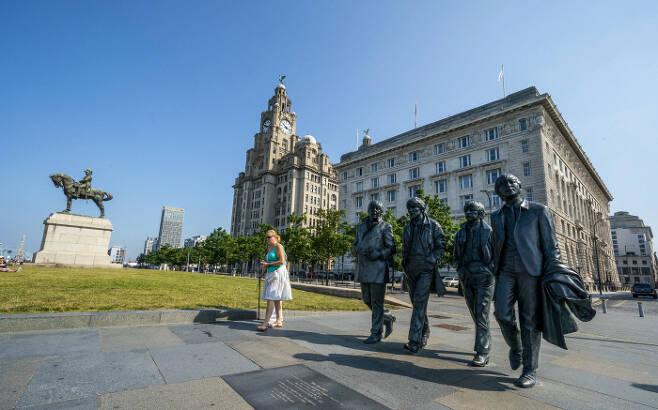영국 리버풀 부둣가의 로열 리버 빌딩 앞에 세워진 록밴드 비틀스의 동상 앞으로 21일(현지시간) 한 시민이 지나가고 있다. 리버풀   AP연합뉴스