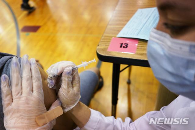 [런던=AP/뉴시스] 지난달 11일 영국 런던 한 중학교에서 의료진이 학생들에게 화이자 백신을 접종하고 있다. 2021.07.22.